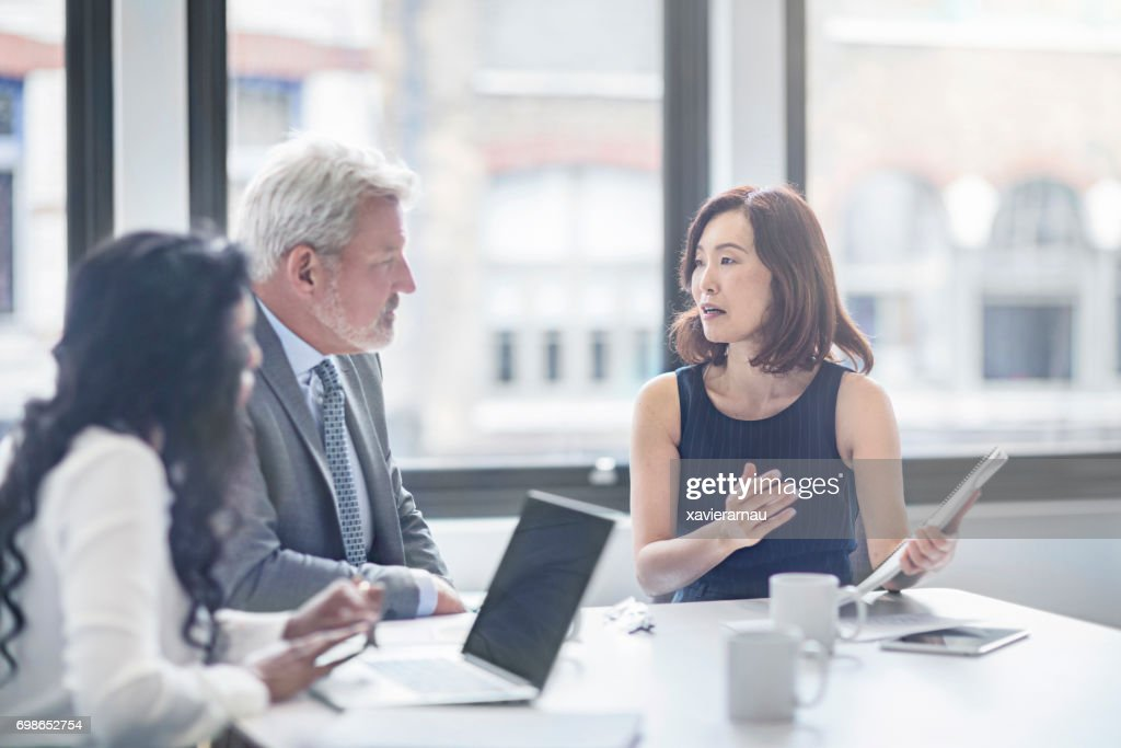 Businesswoman discussing with colleagues in office : Stock Photo