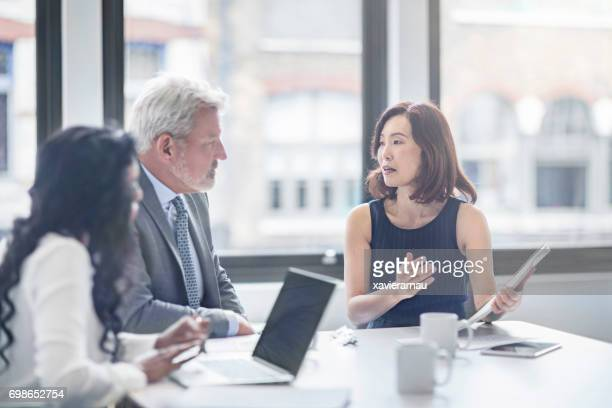 businesswoman discussing with colleagues in office - asian and indian ethnicities stock pictures, royalty-free photos & images