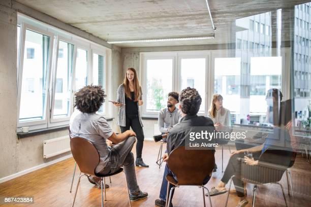 businesswoman discussing with colleagues in office - seminar stock-fotos und bilder