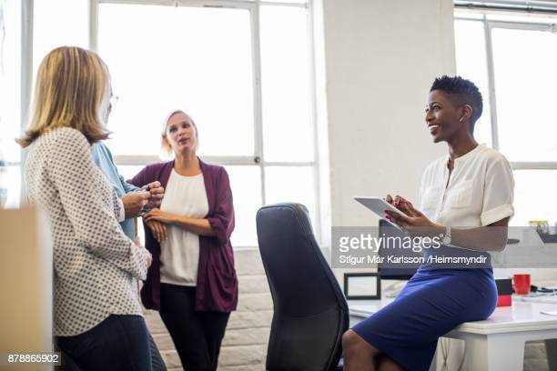 Businesswoman discussing with colleagues in office