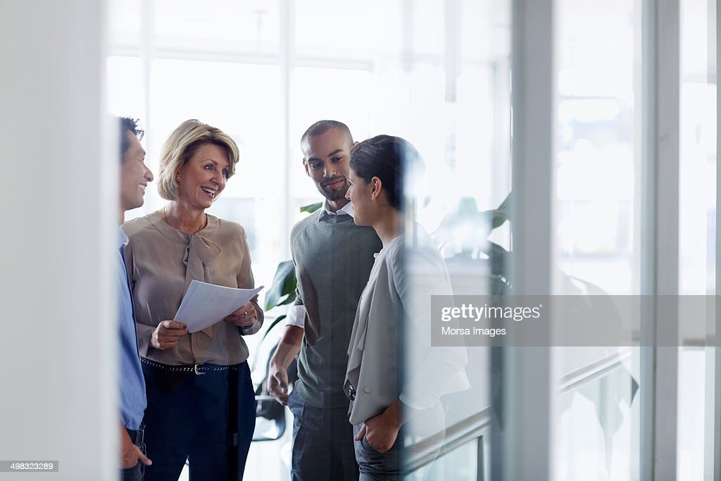 Businesswoman discussing with colleagues : Stock Photo