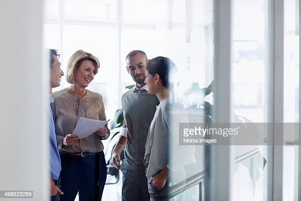 businesswoman discussing with colleagues - zakenbijeenkomst stockfoto's en -beelden