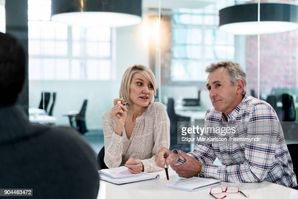 businesswoman discussing with coworkers in office - 50 59 years stock pictures, royalty-free photos & images