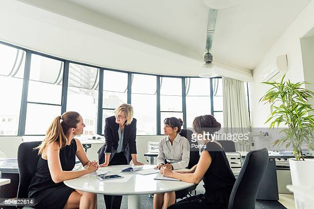 Businesswoman discussing with executives at office