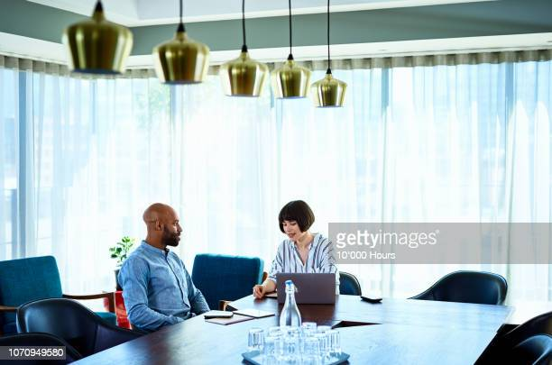 businesswoman discussing with male colleague in conference room - interview stock pictures, royalty-free photos & images