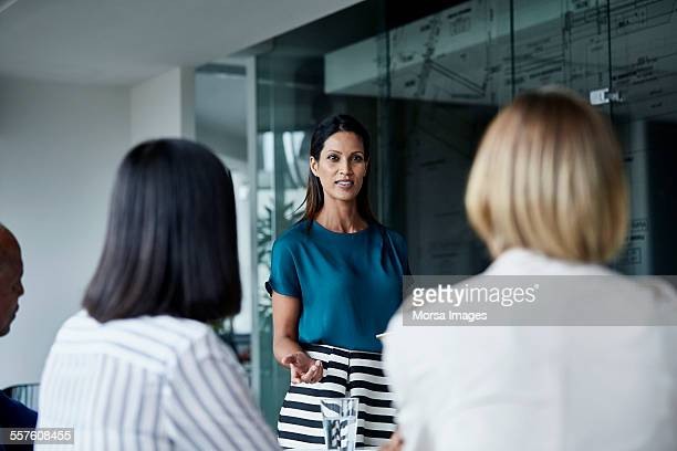 Businesswoman discussing with team in meeting room
