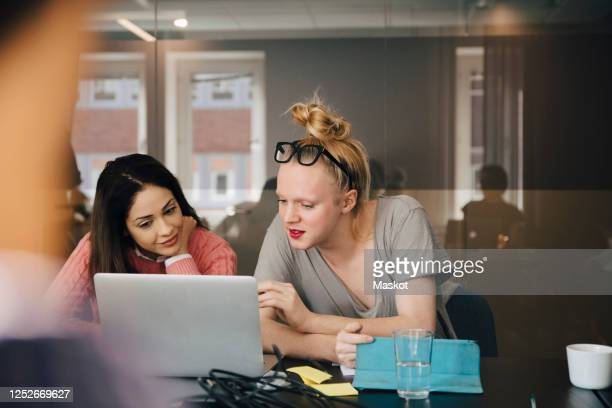 businesswoman discussing with transgender colleague over laptop in board room during meeting - lgbtq stock pictures, royalty-free photos & images