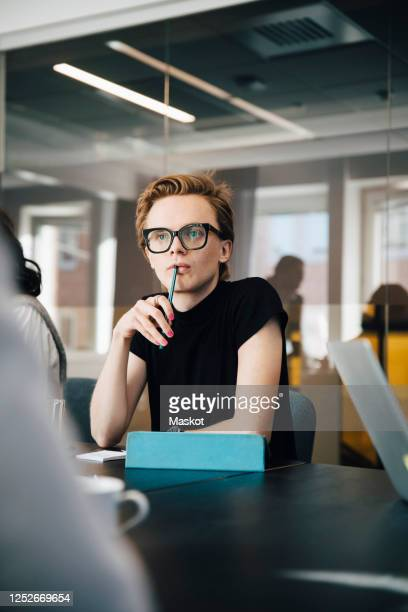 businesswoman discussing with transgender colleague over laptop in board room during meeting - genderblend stock pictures, royalty-free photos & images