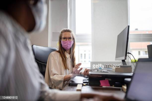 businesswoman discussing work through glass partition with colleague - business stock pictures, royalty-free photos & images
