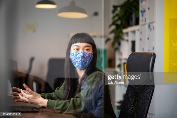businesswoman discussing work with colleague through glass shield on desk - reopening stock pictures, royalty-free photos & images