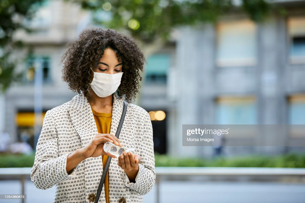 Businesswoman Disinfecting Hands with Hand Sanitizer During Pandemic in city. She is Wearing Protective Face Mask. : Stockfoto