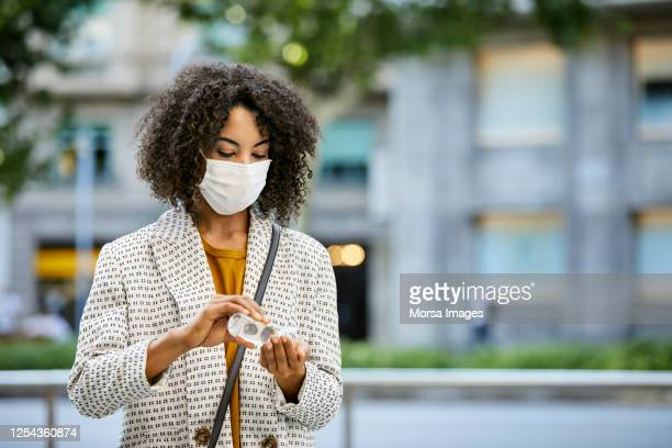 businesswoman disinfecting hands with hand sanitizer during pandemic in city. she is wearing protective face mask. - alcool gel imagens e fotografias de stock