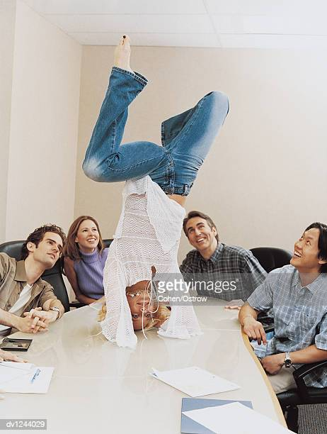 Businesswoman Doing a Handstand on a Table in a Conference Room to the Amusement of Her Colleagues