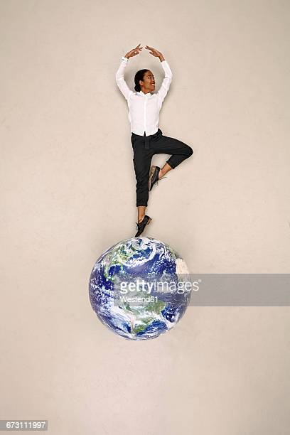 Businesswoman doing a pirouette on globe