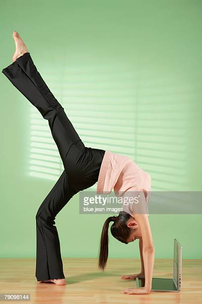 A businesswoman doing body exercise and seeing laptop screen upside down.