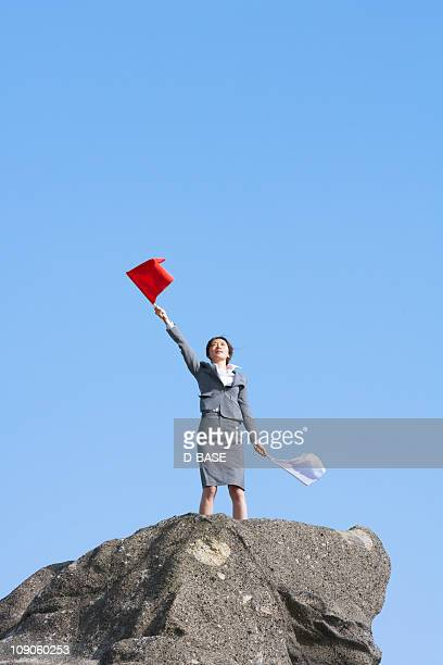 businesswoman doing  flag signaling on the cliff