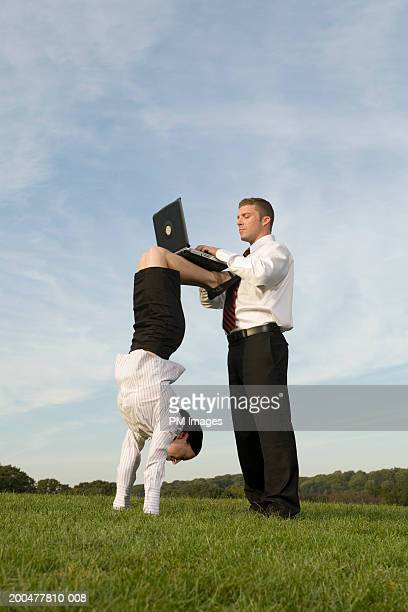 Businesswoman doing handstand, balancing laptop on feet for man