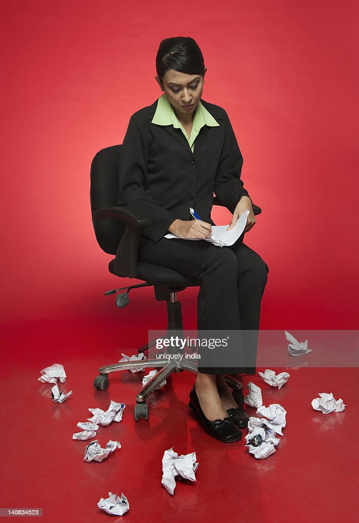 Businesswoman doing paperwork and surrounded with crumpled papers : Stock Photo