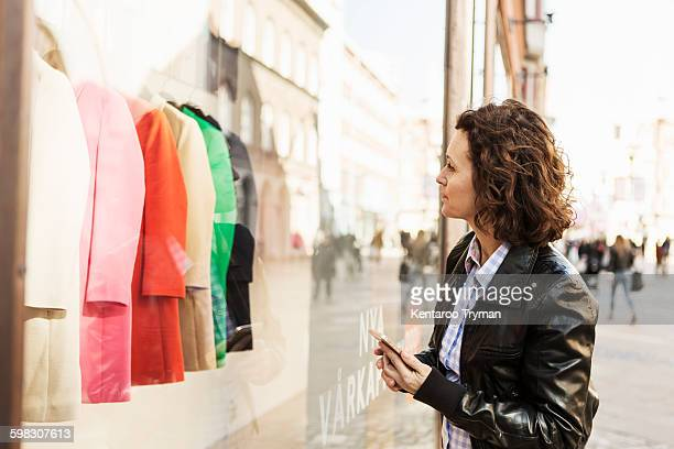 Businesswoman doing window shopping while holding mobile phone in city