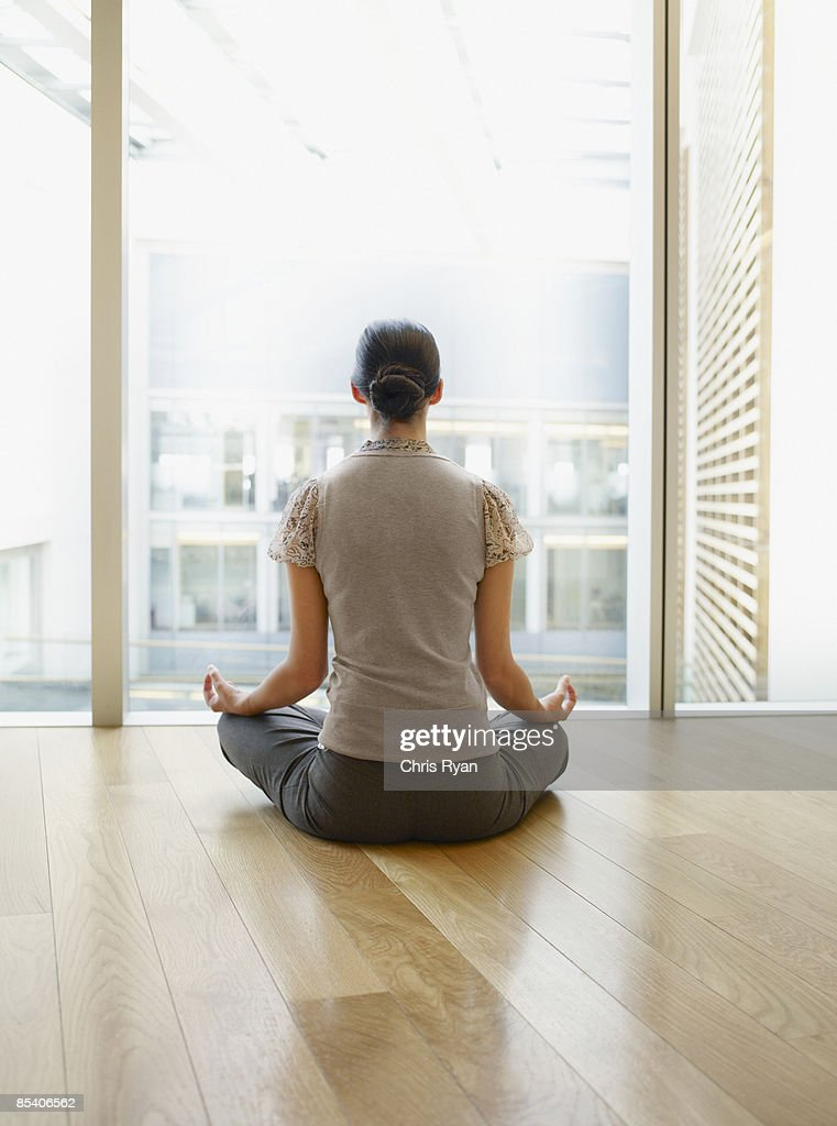 Businesswoman Doing Yoga In Modern Office