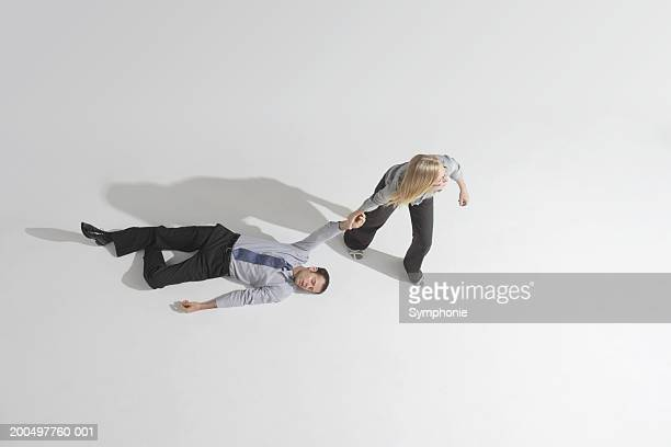 businesswoman dragging male colleague across floor, elevated view - dragging stock pictures, royalty-free photos & images