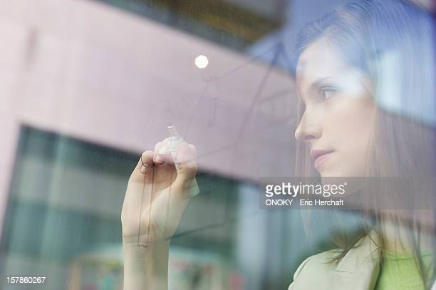 Businesswoman drawing a house on a glass surface