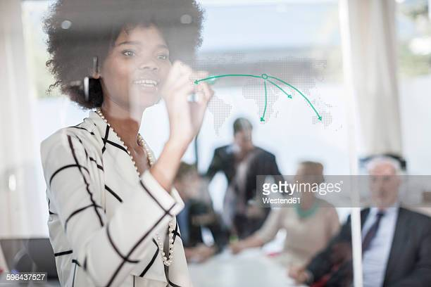 Businesswoman drawing on glass in meeting room