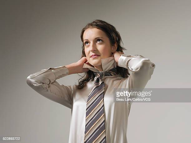 Businesswoman dressing in silk blouse and necktie
