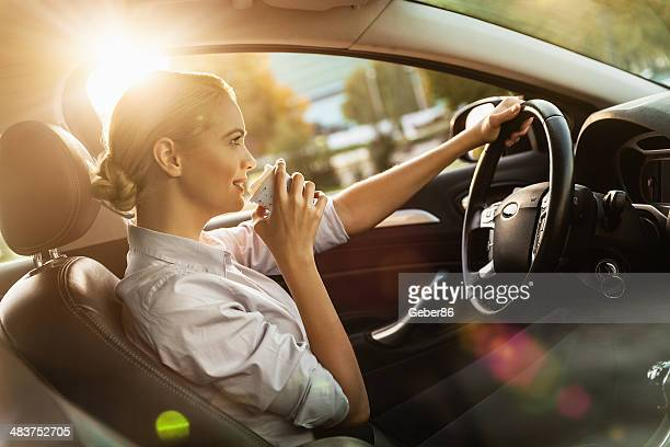 Businesswoman dringking cofee while driving