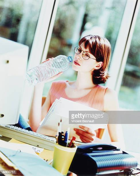 Businesswoman drinking bottled water, working in home office