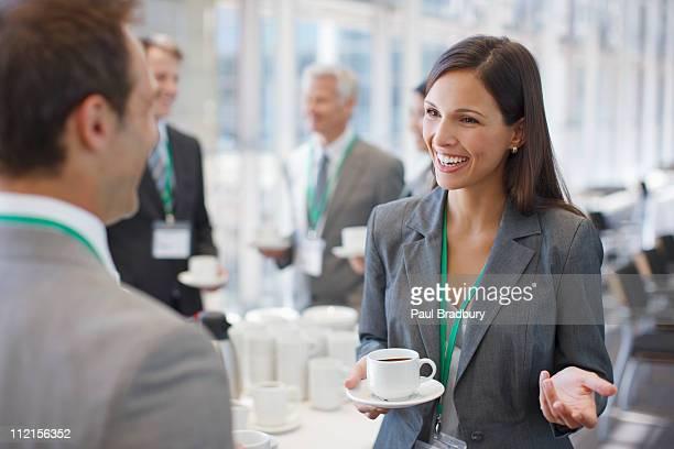 コーヒーを飲みながら、話しているビジネスウーマンに共同作業員