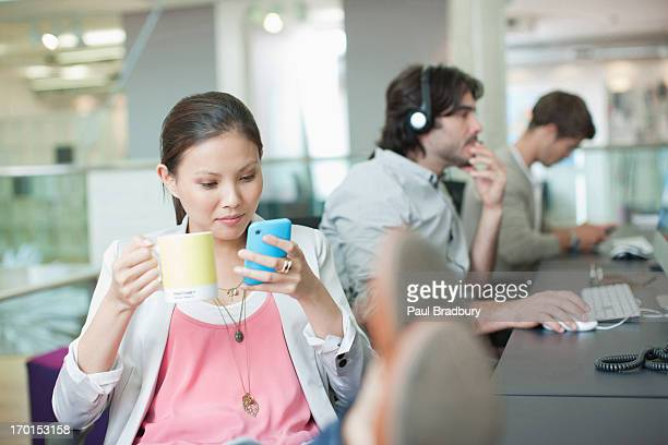 businesswoman drinking coffee and text messaging with feet up in office - wasting time stock pictures, royalty-free photos & images