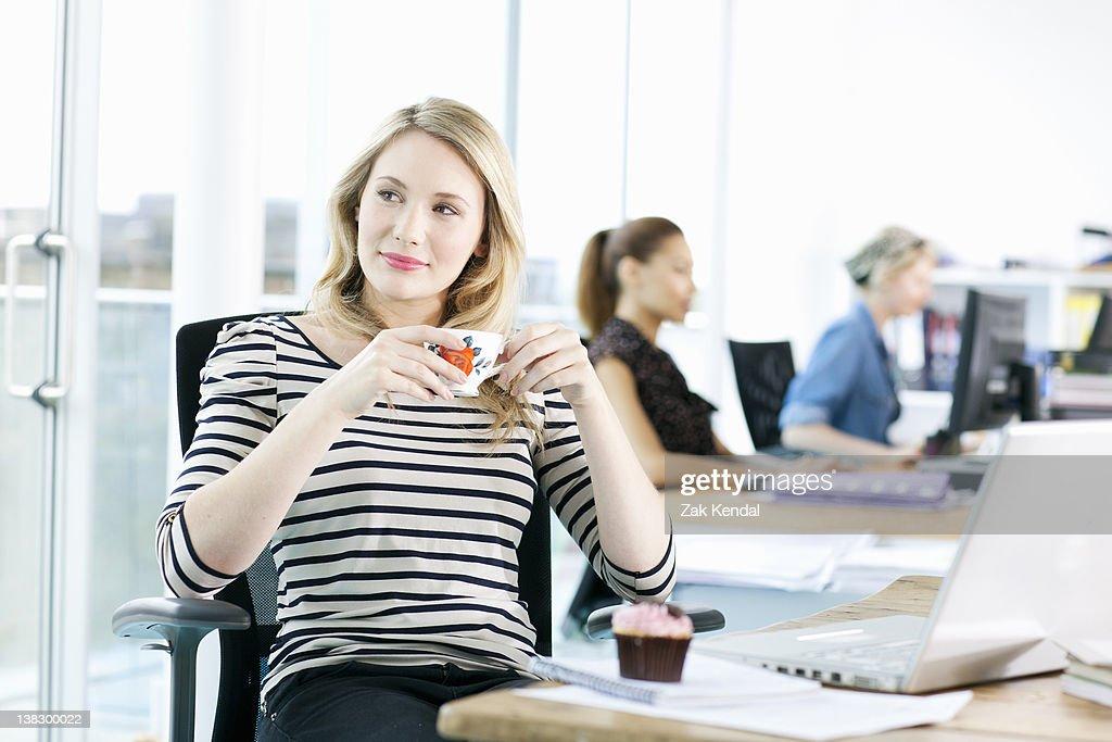 Businesswoman drinking coffee at desk : Stock Photo