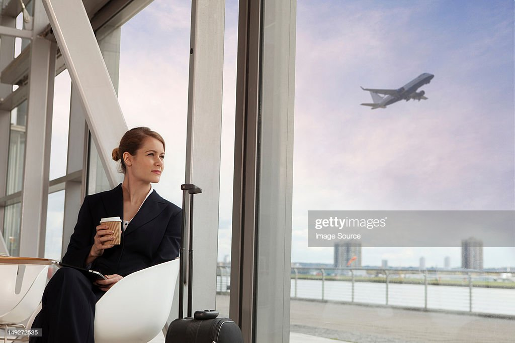 Businesswoman drinking coffee in airport : Stock Photo