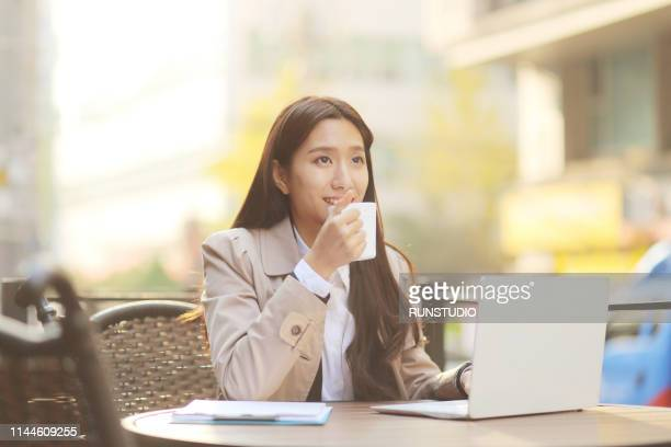 businesswoman drinking coffee in cafe while working on laptop - オープンカフェ ストックフォトと画像