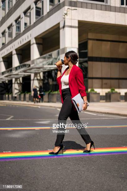 businesswoman drinking coffee to go while crossing the street on lgbt stripes, london, uk - striped blazer stock pictures, royalty-free photos & images
