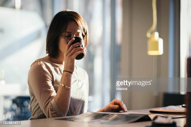 Businesswoman drinking coffee while reading document at desk in office