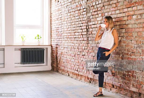Businesswoman drinking cup of coffee at brick wall in office
