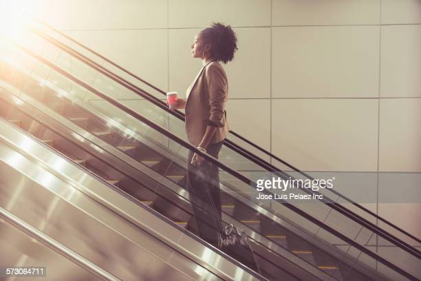 Businesswoman drinking cup of coffee on escalator