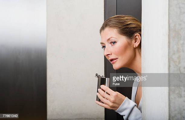 Businesswoman Drinking from Flask