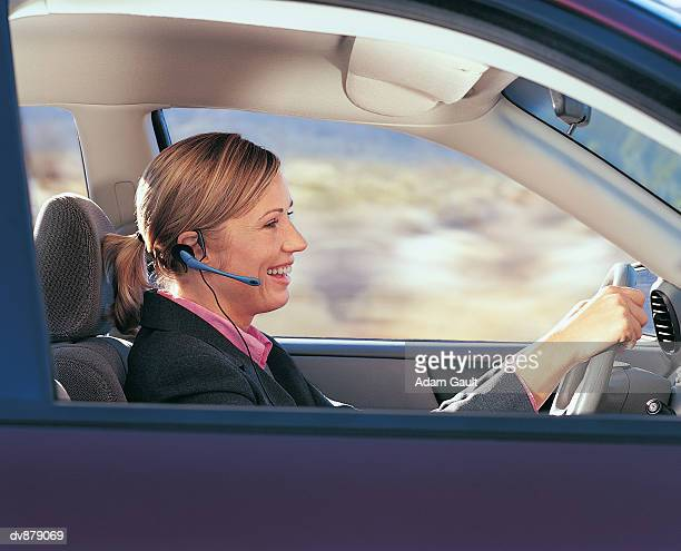 Businesswoman Driving a Car and Using a Hands Free Device to Talk Into Her Mobile Phone