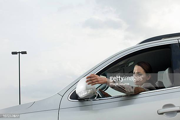 Businesswoman driving car, adjusting wing mirror