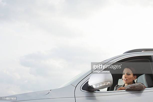 Businesswoman driving car, looking in wing mirror