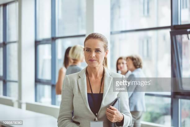 businesswoman during break in seminar - izusek stock photos and pictures