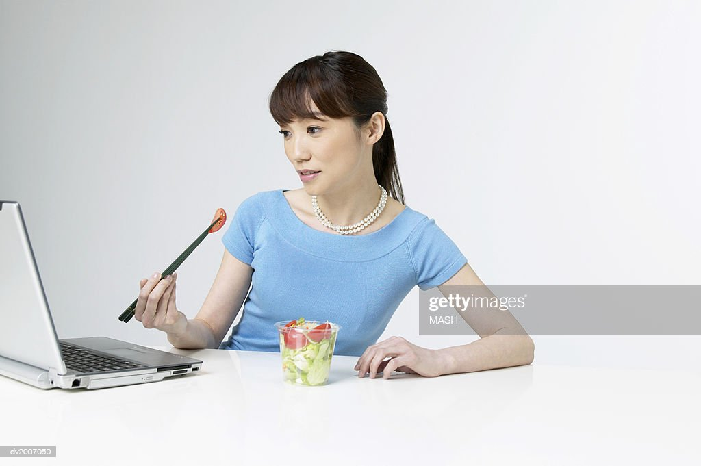 Businesswoman Eating a Salad at Her Desk : Stock Photo