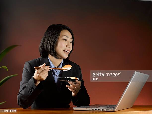Businesswoman eating and working at desk