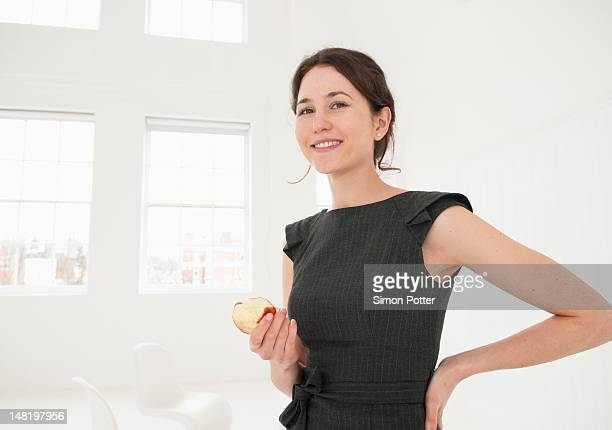 Businesswoman eating apple in office