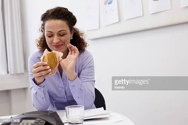 Businesswoman eating at desk in office