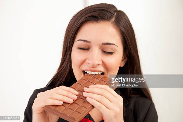 Businesswoman eating bar of chocolate