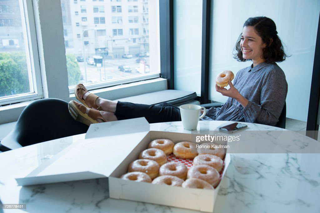 Businesswoman eating donut in conference room : Stock Photo